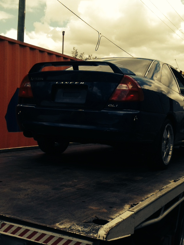 Car removal in action. Nissan car being towed.
