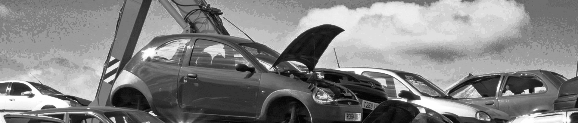 Crane lifts a wrecked car and places it on a pile of scrap cars at our car wrecking yard. Shown on bigger screens than mobile phones.